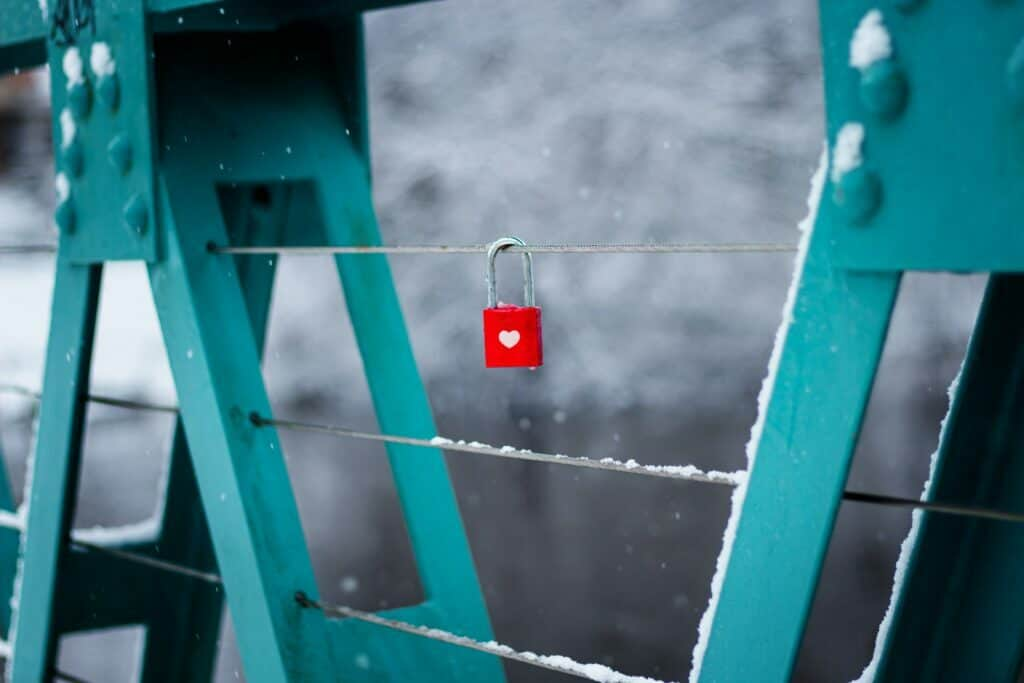 red lock with a white heart locked on a bridge railing representing customer retention