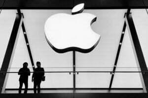 silhouette of people standing below white apple logo ios 15