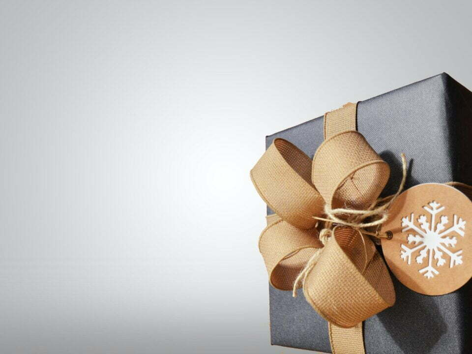 picture of present with blue wrapping paper, gold ribbon tied up in a bow and a label with a snowflake on it in front of a greay background, for christmas marketing planning article