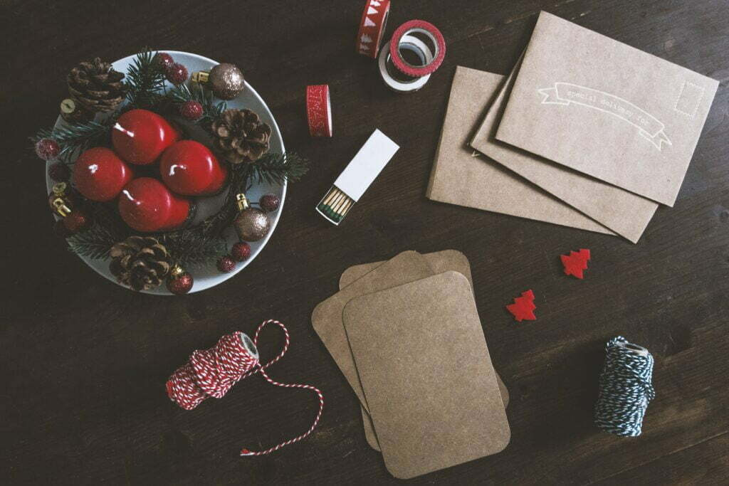 collection of christmas crafts on dark wooden table, including postcards, envelopes, christmas-themed string and tape, and a bowl of four red candles with pinecones and baubles placed around them, for christmas marketing planning article